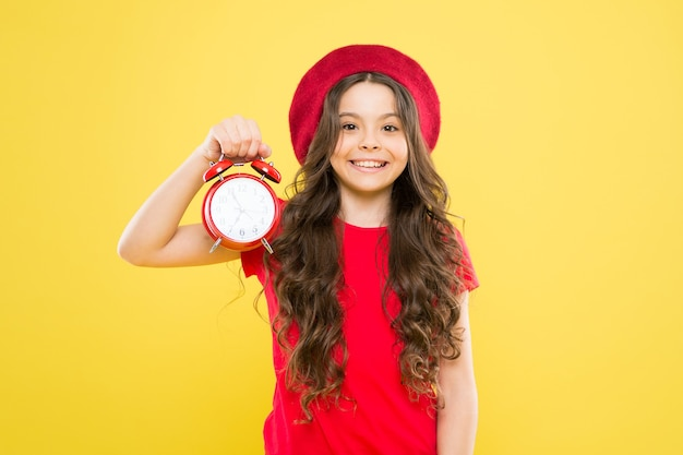 Little girl in french style hat. beauty hairdresser and fashion. child with alarm clock. timeless fashion. parisian child. happy girl with long curly hair in beret. fashion is fleeting. fashion time.