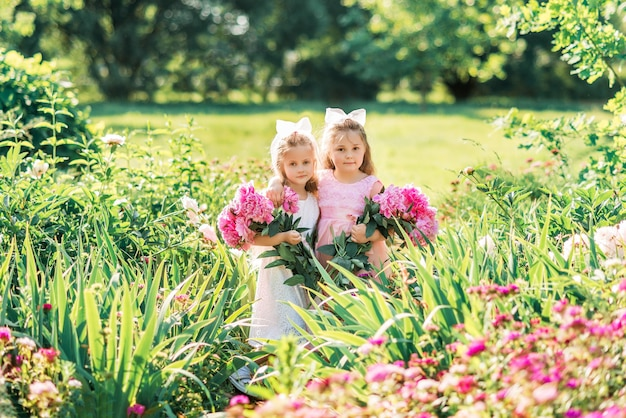 Маленькая девочка дружит с большим букетом пионов. дети гуляют летом в парке с цветами.