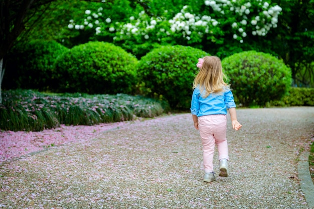 Little girl from behind walking in park. child enjoy life without allergy.