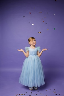 A little girl in a full-length blue princess dress catches flying confetti with her hands on purple