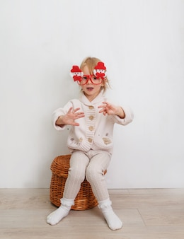 A little girl in funny christmas glasses with snowmen is sitting against a white wall.