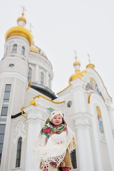 A little girl in a fur coat and a russian scarf on the surface of an orthodox church