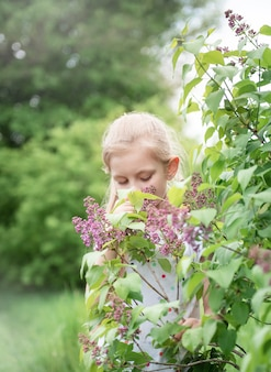 Little girl in the garden near the lilac bushes