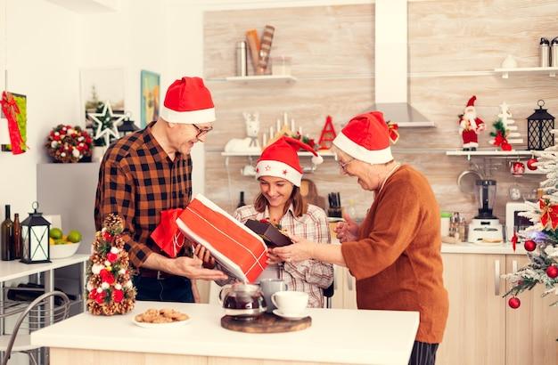 小さな女の子はクリスマスのギフトボックスに驚かされます