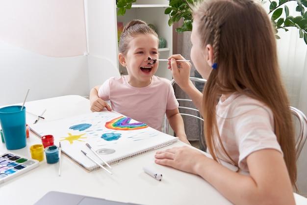 テーブルで姉によって描かれた彼女の顔を得る少女