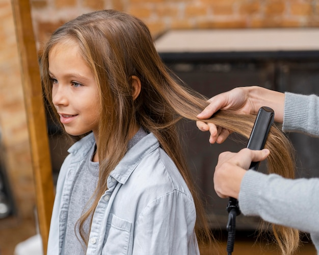 Little girl getting her hair straightened by beautician