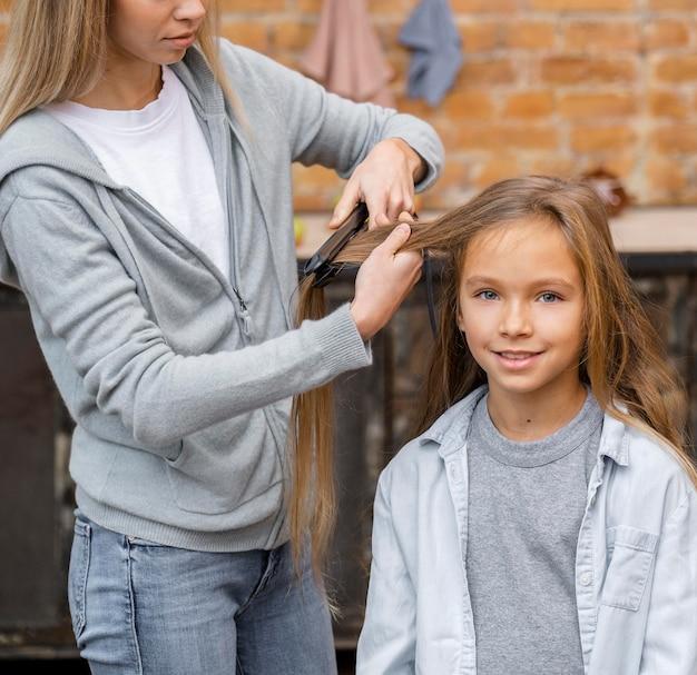 Little girl getting her hair straightened by hairdresser
