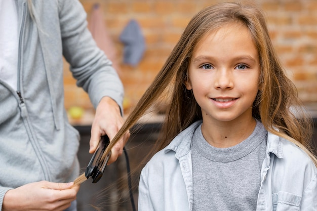 Little girl getting her hair straightened by hairstylist