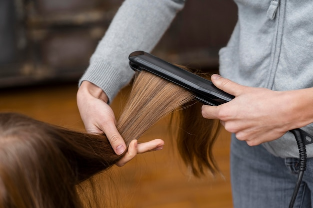 Little girl getting her hair straightened