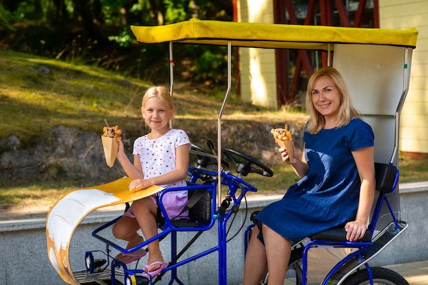 A little girl and a girl in a blue dress are sitting on a family bike and holding a delicious and beautiful ice cream in a waffle with sprinkles and sweets.