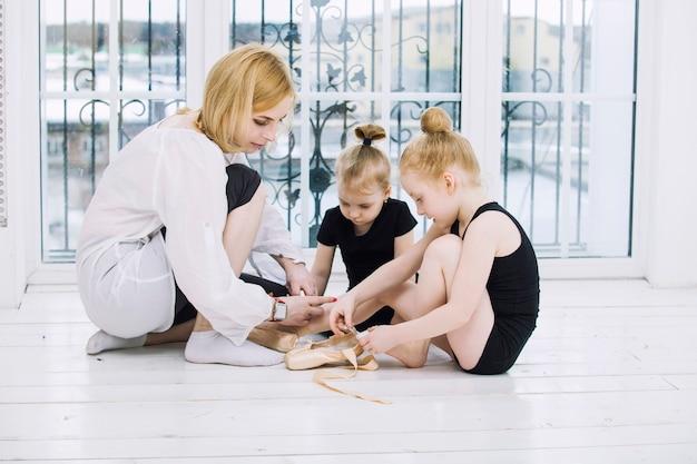 어린 소녀 소녀 발레리나와 댄서는 행복하고 귀여운 밝은 방에서 여성 코치와 함께 스트레칭을하고