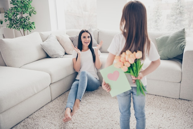 Little girl give mommy flowers bouquet greeting card in house indoors