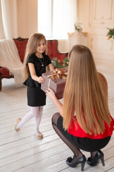 Маленькая девочка дарит маме коробку с рождественским подарком.