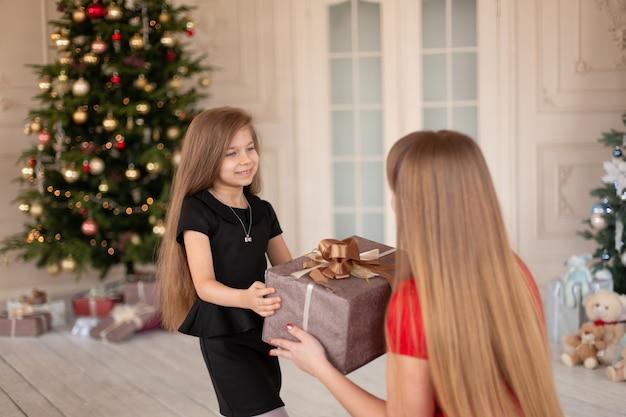 小さな女の子は彼女のお母さんにクリスマスプレゼントの箱を渡します。