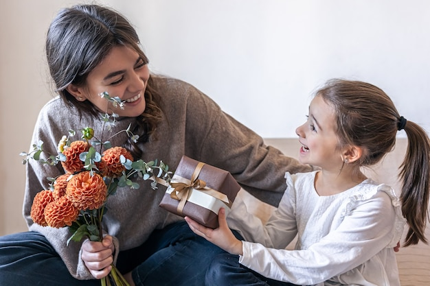 A little girl gives her mother a gift and a bouquet of flowers