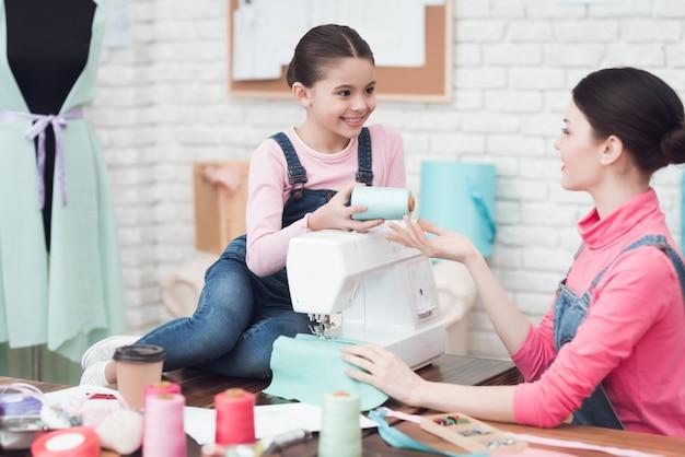 A little girl gives a woman threads.