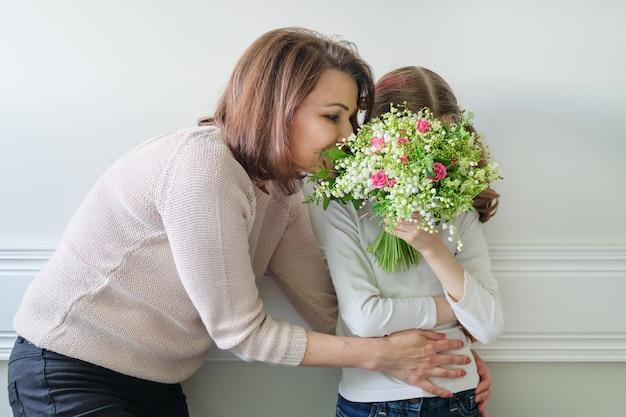 Маленькая девочка дарит букет своей матери