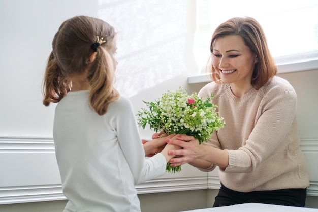 Little girl giving a bouquet to her mother
