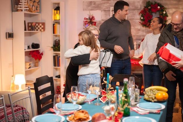 Маленькая девочка обнимает бабушку на рождественском семейном ужине.