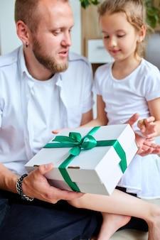 Маленькая девочка дарит своему красивому отцу подарочную коробку в день отца