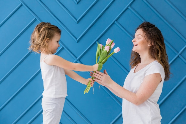 Little girl giving pink tulips flowers to her mom on mother's day in front of blue background