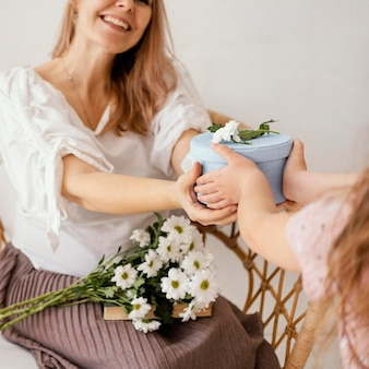 Little girl giving spring flowers and gift box to mom