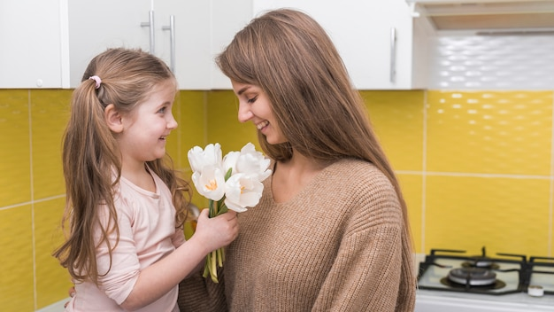 Little girl giving tulips to mother