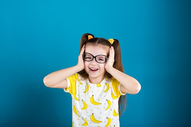 Little girl in glasses and banana t-shirt on blue background