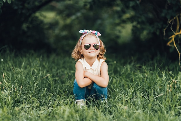 Little girl in glasses and dresses posing outdoors