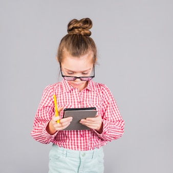 Little girl in glasses using tablet