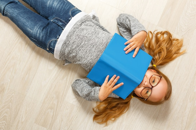 Little girl in glasses with a book lying on the floor
