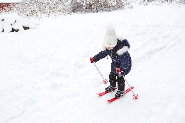 A little girl glides down the slope in red plastic skis.