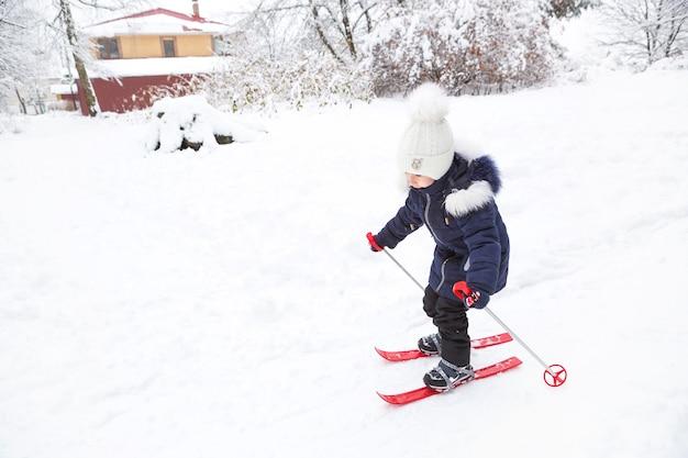 小さな女の子が棒で赤いプラスチックスキーで斜面を滑り降りる