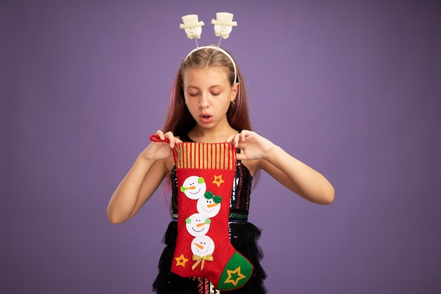 Little girl in glitter party dress and funny headband holding christmas stocking looking inside intrigued standing over purple background