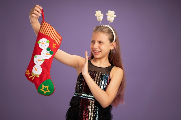 Little girl in glitter party dress and funny headband holding christmas stocking looking at it displeased holding hand out standing over purple background