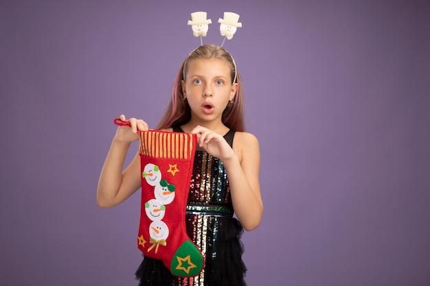 Bambina in abito da festa glitter e fascia divertente che tiene la calza di natale sorpresa in piedi sopra la parete viola