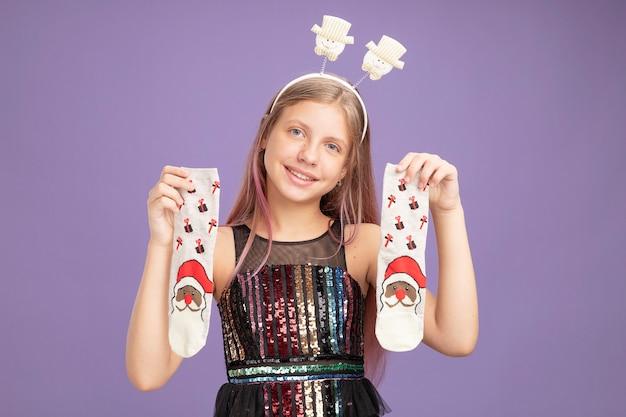 Bambina in abito da festa glitterato e fascia divertente che tiene le calze di natale guardando la telecamera sorridendo allegramente in piedi su sfondo viola