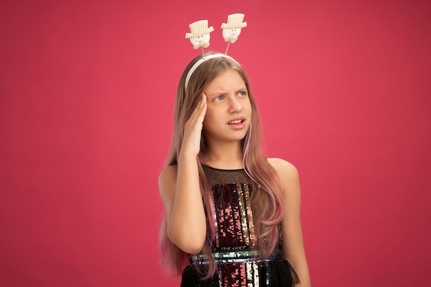 Little girl in glitter party dress and funny headband looking aside puzzled, new year celebration holiday concept standing over pink background