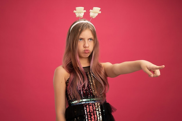 Little girl in glitter party dress and funny headband looking aside with serious face pointing with index finger at something new year celebration holiday concept standing over pink background