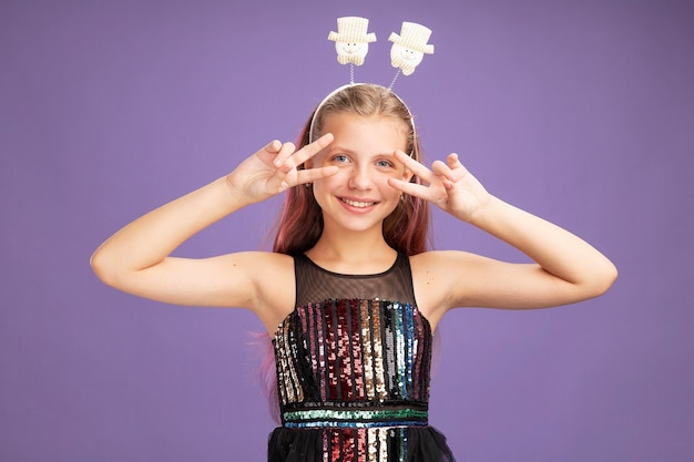 Little girl in glitter party dress and funny headband looking at camera showing v-sign near ger eyes smiling cheerfully standing over purple background