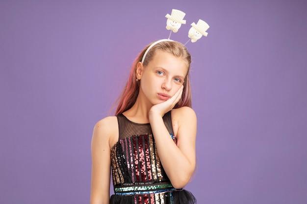Bambina in abito da festa glitterato e fascia divertente che guarda la telecamera stanca e infastidita in piedi su sfondo viola