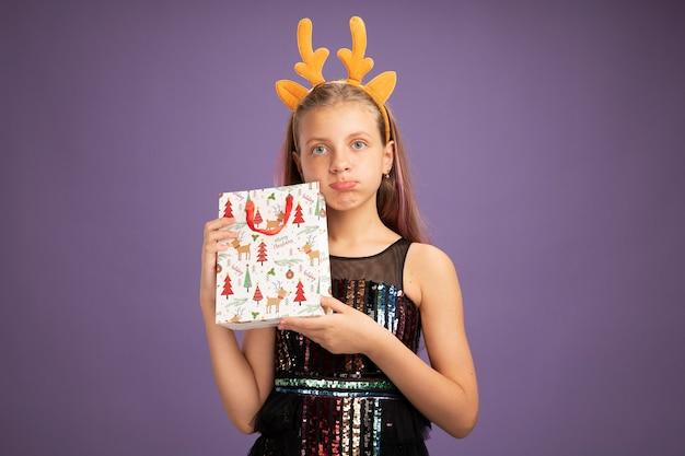 Bambina in abito da festa glitter e fascia divertente con corna di cervo che tiene un sacchetto di carta di natale con regali guardando la telecamera dispiaciuta in piedi su sfondo viola