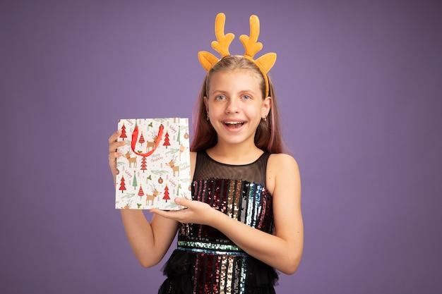 Bambina in abito da festa glitter e fascia divertente con corna di cervo che tiene il sacchetto di carta di natale con regali che guarda l'obbiettivo felice ed eccitato in piedi su sfondo viola