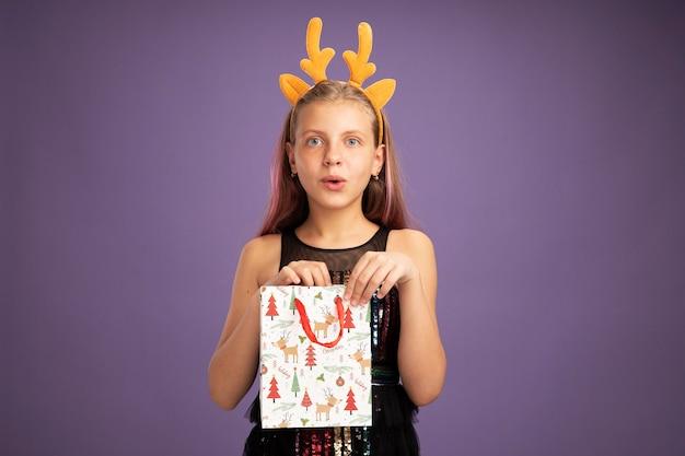Bambina in abito da festa glitter e fascia divertente con corna di cervo che tiene il sacchetto di carta di natale con regali che guarda l'obbiettivo felice e sorpreso in piedi su sfondo viola