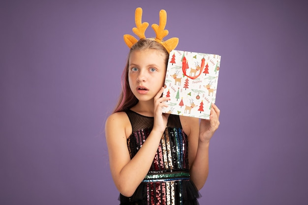 Little girl in glitter party dress and funny headband with deer horns holding christmas paper bag with gifts looking at camera intrigued and surprised standing over purple background