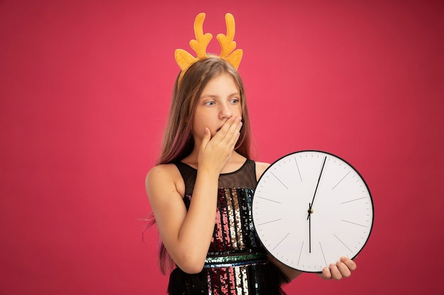 Little girl in glitter party dress and funny headband with deer horns holding clock looking aside amazed covering mouth with hand, new year celebration holiday concept standing over pink background