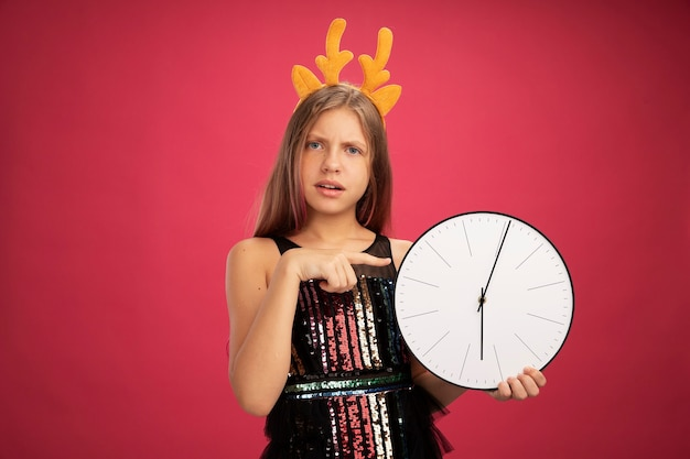 Little girl in glitter party dress and funny headband with deer horns holding clock pointng with index finger at it looking confused, new year celebration holiday concept standing over pink background