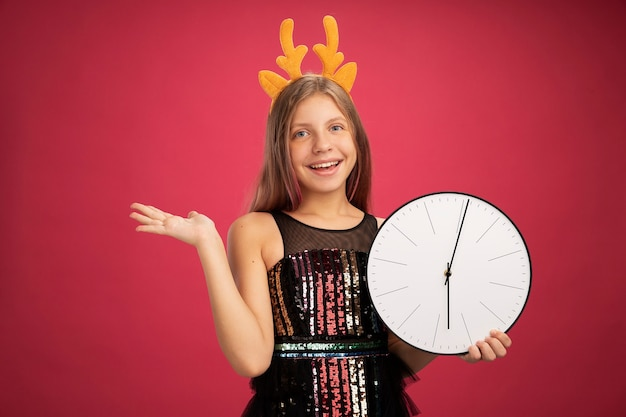 Little girl in glitter party dress and funny headband with deer horns holding clock smiling with happy face with arm raised new year celebration holiday concept standing over pink background
