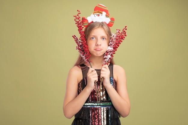 Bambina in abito da festa glitterato e fascia con babbo natale che tiene rami con bacche rosse che guarda l'obbiettivo con espressione triste che increspa le labbra in piedi su sfondo verde