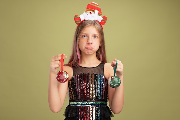 Little girl in glitter party dress and headband with santa holding christmas balls looking at camera confused and displeased standing over green background